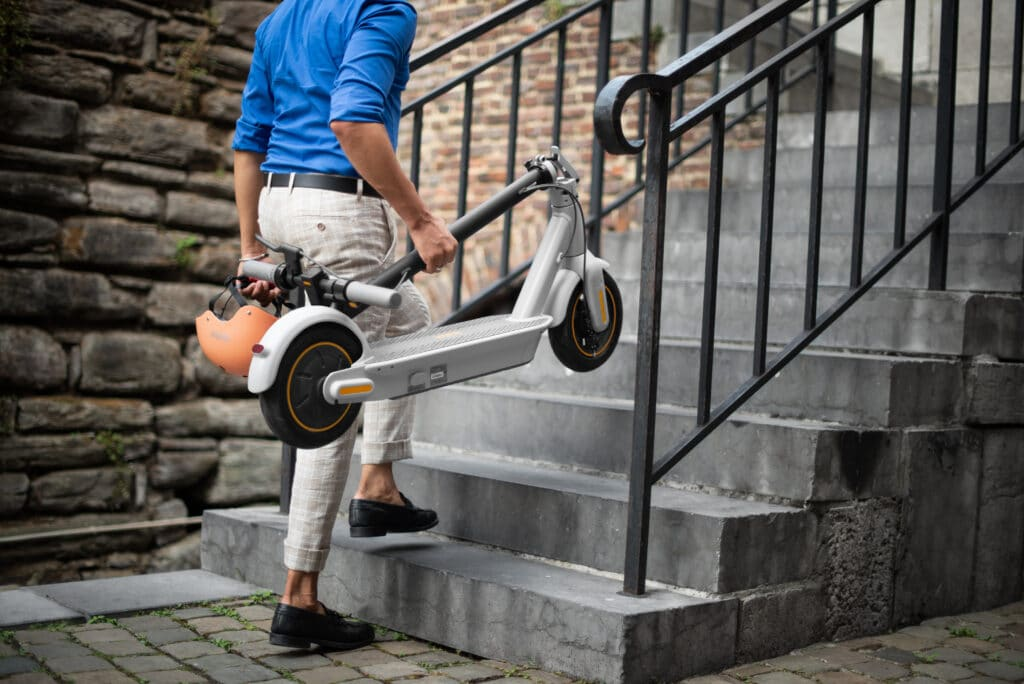 MAX-G30LE_Lifestyle_Holding-folded-KickScooter-1024×684